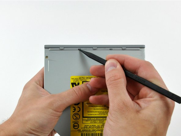 Image 1/2: Use the tip of a spudger to push the two plastic bezel tabs away from their retaining slots on the top of the optical drive.