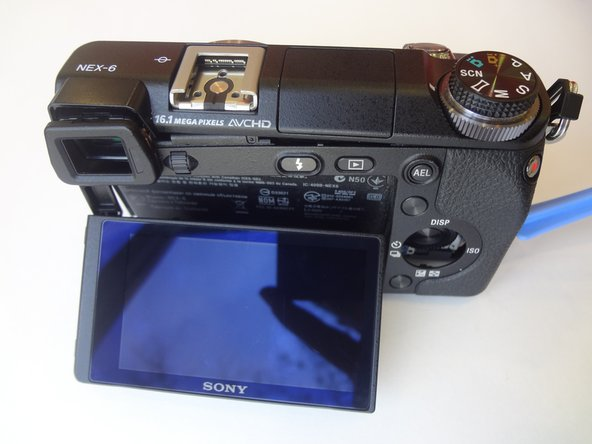 Image 2/2: Gently lift the back case away from the camera an slide it down to completely remove the back case.