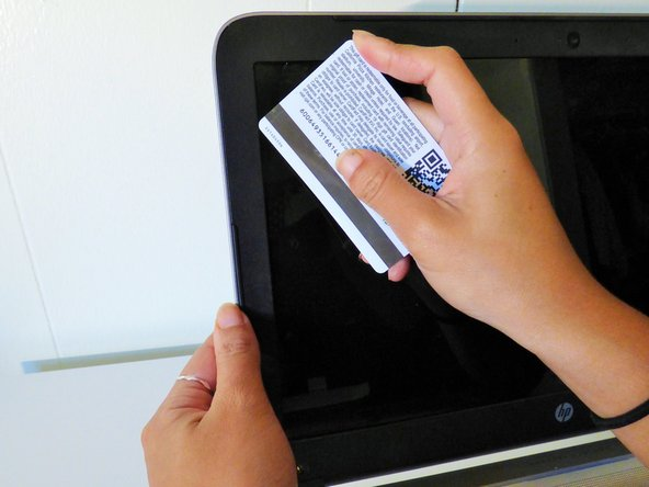 Use the plastic card or your fingernail to separate the black plastic border from  the screen case.