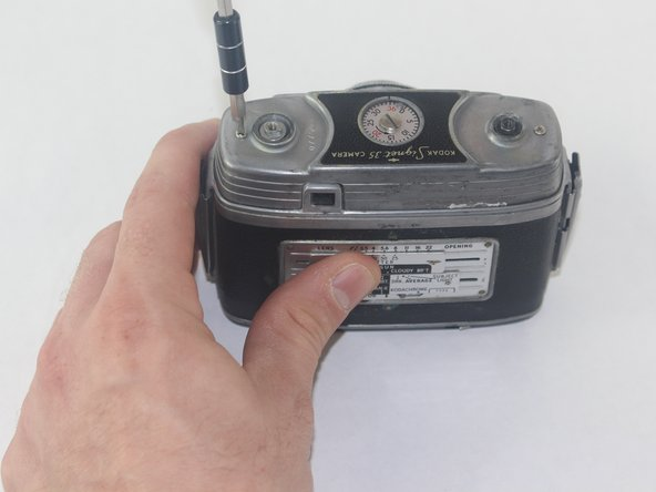 Image 2/3: While holding the camera with one hand, use the other hand to remove the top of the camera.