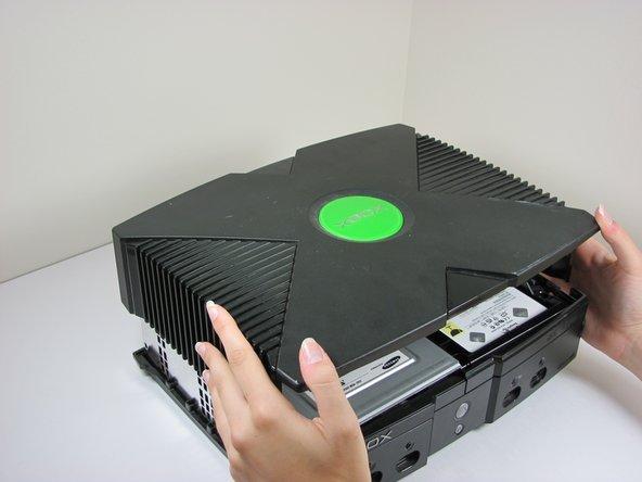 Una vez que las carcasa inferior y superior ya no están conectadas, gire cuidadosamente la Xbox hacia la derecha, levante y retire la cubierta superior.