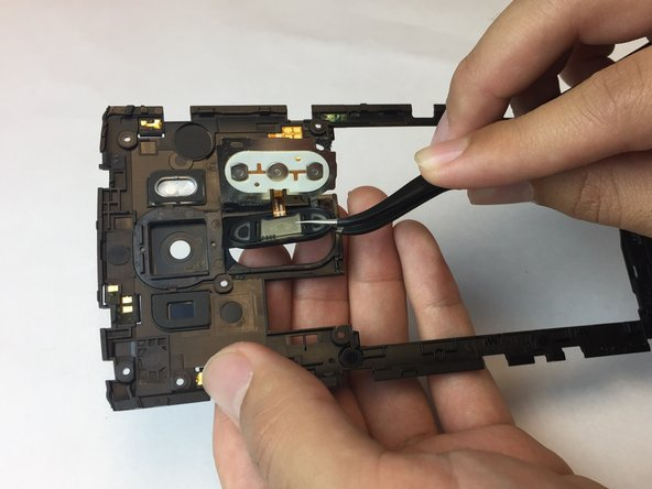 Use your finger to pop the power button and fingerprint sensor out of its slot in the back panel; there should be a plastic frame around the power button/fingerprint sensor component.
