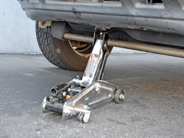 Image 1/3: Place the jack back under the lifting point. Lift the car until the jack stand is no longer supporting the car. Remove the jack stand.