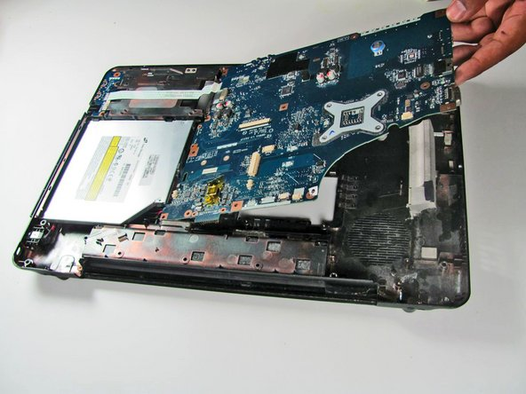 After all the screws are removed, lift the motherboard up and away from the earphone jacks that are located at the front of the laptop.