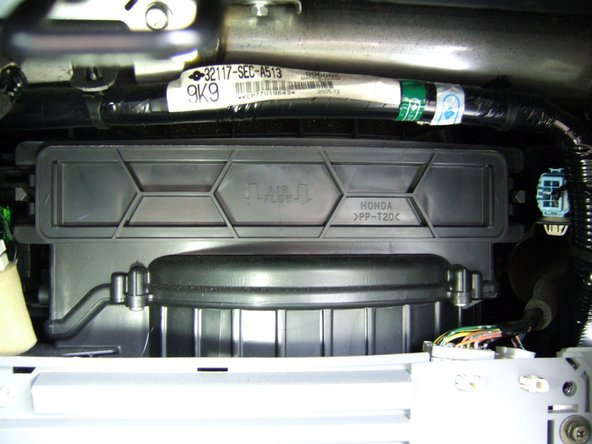 With the glove box now lowered, the heater blower unit is visible. At the top of the blower is the air filter tray.