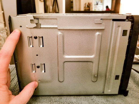 For Drobo 5D (and possibly others), you need only remove 2 screws (of the 4) on each side before sliding the back plate off.