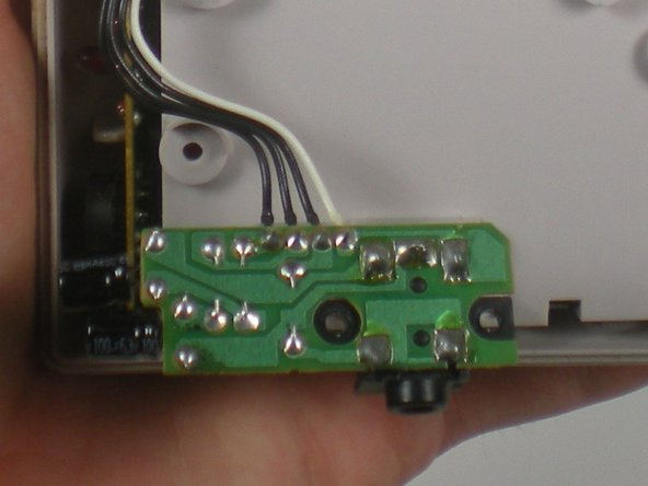 Once the headphone jack is detached it will dangle by the wires attached to the main circuit board. Do not worry about the connections, they are solid and will not break.