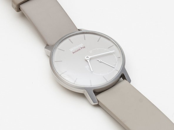 This is Withings Activité Pop Smartwatch. A beautifully designed no frills smartwatch that shows your daily activity score with an analogue gauge. Remove the rubber band by pulling tiny levers at the back along arrow direction.