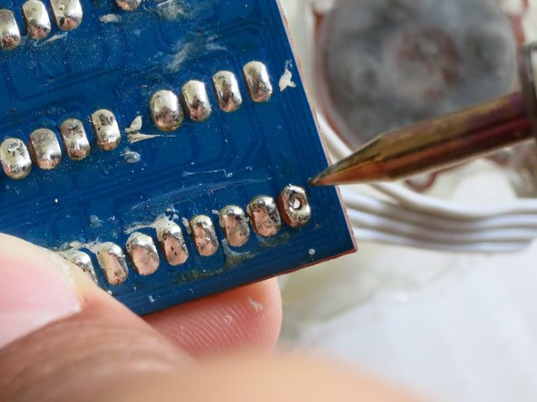 Once the solder begins melting, add a little pressure and you will be able to find a hole through the board.
