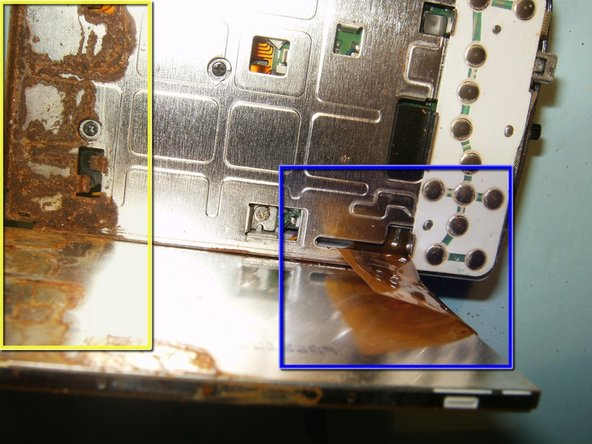Flip the LCD screen away from the top of the device to reveal the ribbon cable.