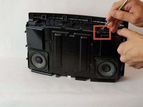 Using a metal spudger or a prying tool, gently push forward to separate the cover from the speaker.
