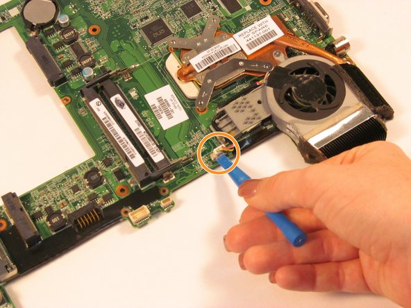 Image 2/2: Using a plastic opening tool, disconnect the wire that attached the fan to the board.