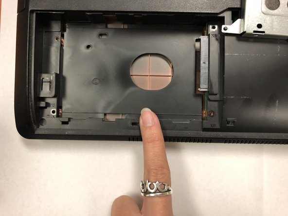 Detach the hard drive by sliding it to the left.