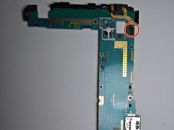 Turn the motherboard around and use the pry tool to remove the front camera connector.
