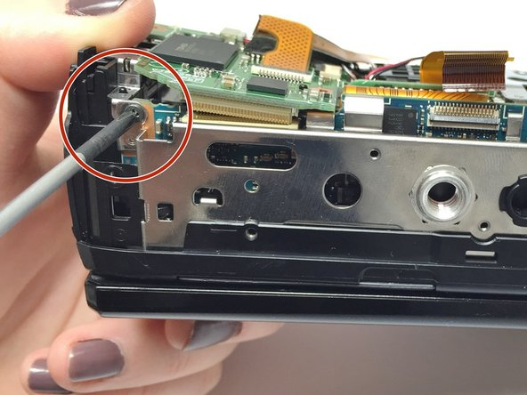 Image 1/2: The green motherboard should now be partially detached, as shown in the photo.