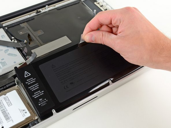 Image 1/1: Use the attached plastic pull tab to remove the battery from the upper case.