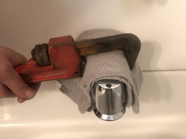Adjust your pipe wrench so that it fits over the rag and is snug against the bathtub spout.