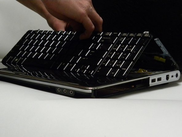 Image 1/2: Lift the keyboard from the base. It will still be attached to the system board.