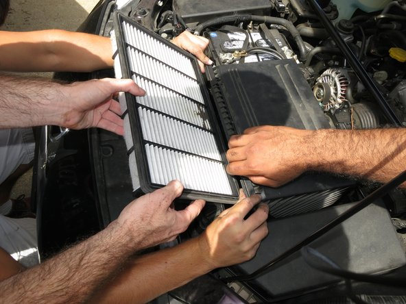 Gently pull the entire air filter out of the opened cover. This might take more than one set of hands in order to keep the cover open during removal.