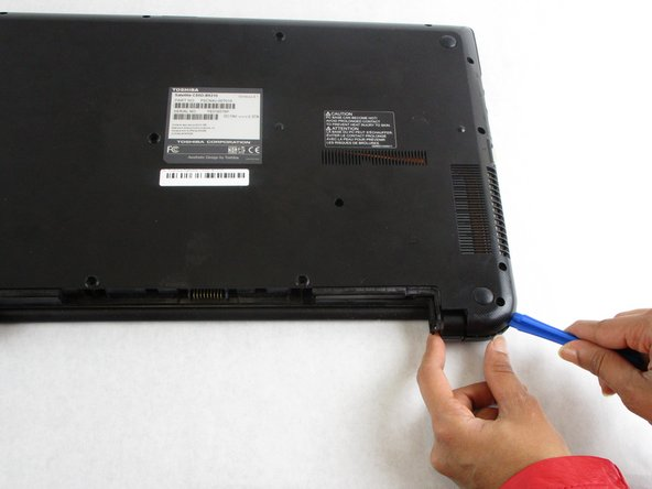 Using the plastic opening tools, separate the back cover from the laptop.
