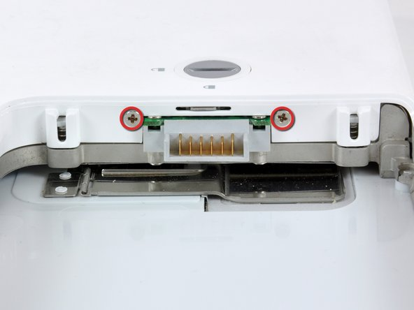 Remove the two Phillips screws on either side of the battery contacts.