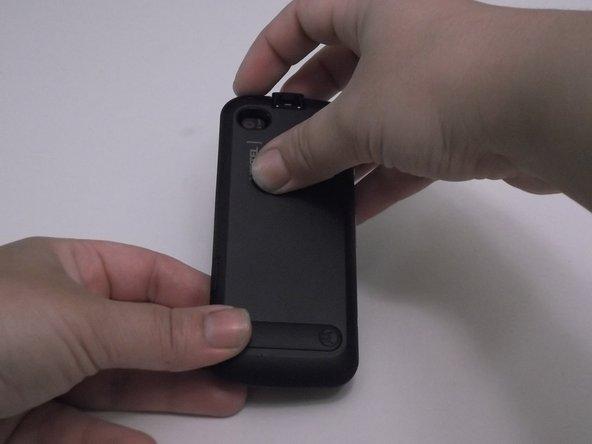 Détachez la prise casque et le couvercle du port USB avec le bout de votre doigt. Placez votre majeur dans l'encoche sur le côté supérieur gauche de l'arrière du téléphone.