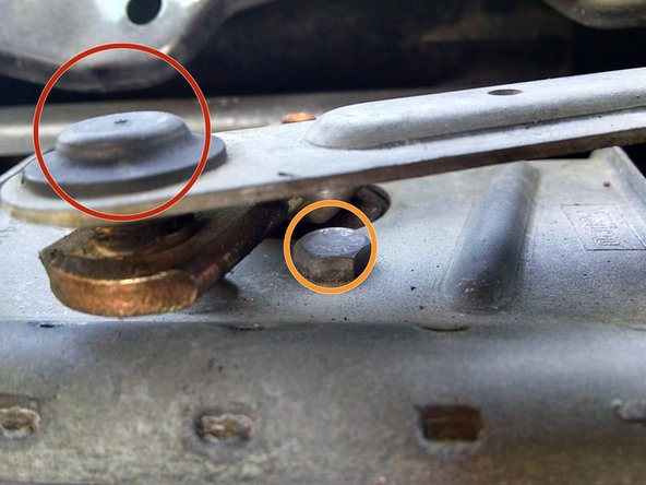 Remove the three motor bolts with a 10mm wrench or socket (orange circles).