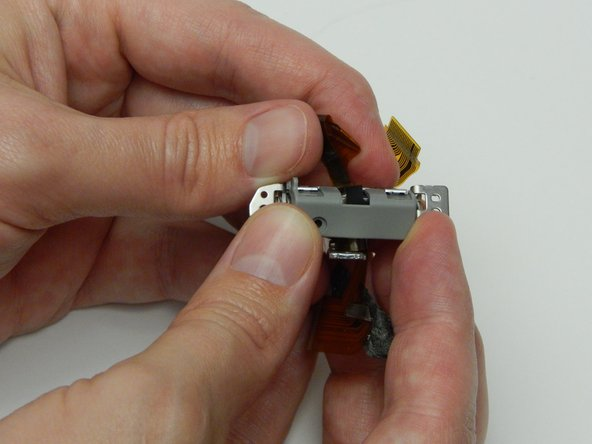 Image 2/3: While grasping the metal section of the assembly, remove the plastic covering that was attached with the clips.
