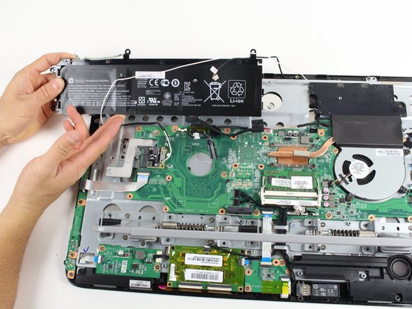Gently remove the battery from the computer, making sure not to tug on any of the cables or wires during the removal.
