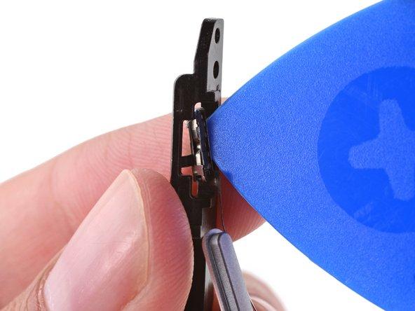 Verwende die Spitze eines Plektrums, um das Ende des Drehsperr-/Mute-Schalters des Tastenkabels von der Tastenhalterung zu lösen.