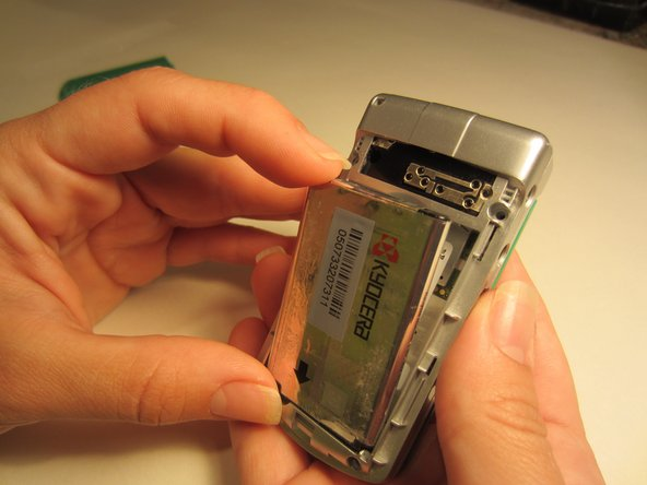 Use your index finger at the top of the battery and pull it towards your body.