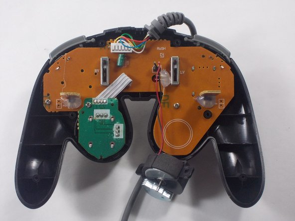 Once your rumble motor is out, you'll see a green part on the motherboard. Unscrew it from the mother board, and pull it up. Attached to this green part is the c-stick. Firmly but gently pull the c-stick off, and clean in and around that area before reattaching.