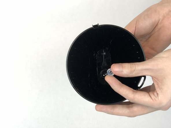 While pressing up on the drip spring mechanism, remove the clear round plastic retainer holding the mechanism in place.