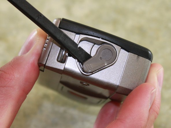 Locate the film door latch located on the side of the camera.