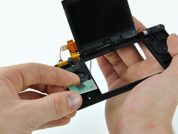 Lift the Wi-Fi antenna up, and pull its cable through the hole in the front display bezel.