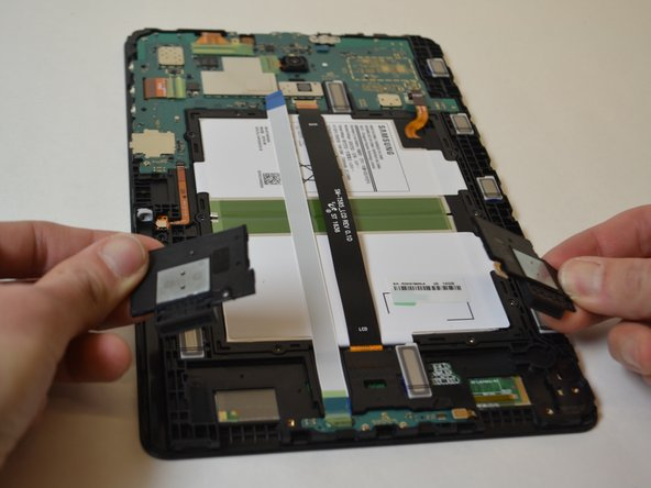 Use a plastic opening tool to pry the speakers out of the tablet