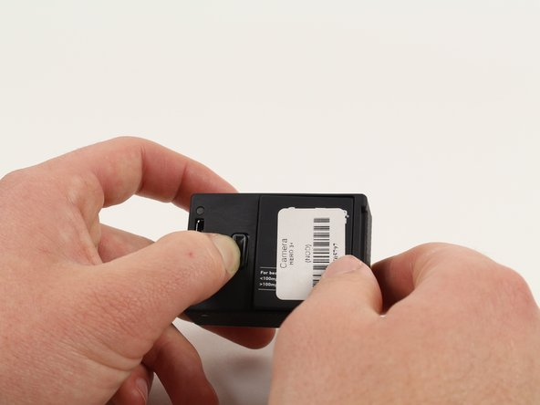 Push the tab on the back of the device left to remove the plate covering the battery.
