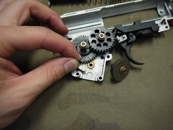 Image 2/3: Remove the three gears and the anti-reversal latch. Be careful not to misplace any of the shims or bushings, or the anti-reversal latch spring.