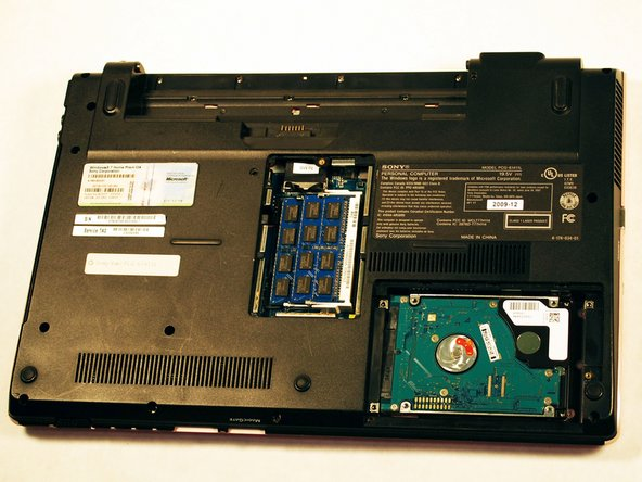 Remove the hard drive by gently pressing down on it and sliding it to the right.