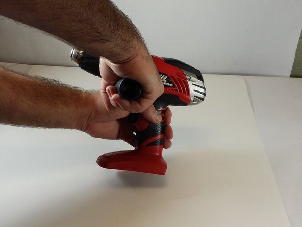 Grip cordless drill firmly with left hand. Grip the cordless drill handle firmly with the right hand. Rotate the handle counterclockwise in order to remove the handle from the drill.