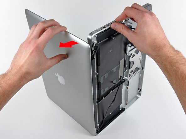 Image 2/3: Lift the display away from the upper case, minding any brackets or cables that may get caught.