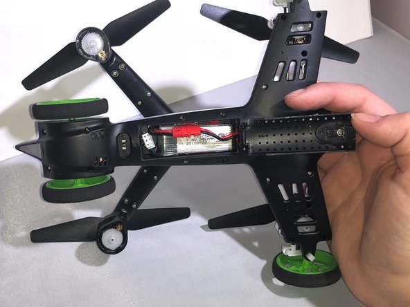 Pull down the battery cover on the bottom of the drone and open it.