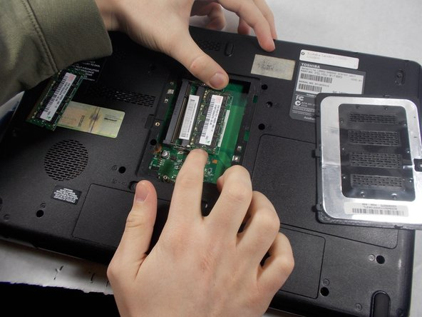 You'll need to do the same as the top for the bottom set of RAM, so gently push outward on the metal pieces above and below the RAM.