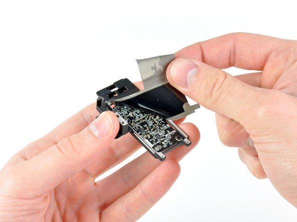 Continue peeling the EMI tape off the bottom of the AirPort/Bluetooth bracket and remove it from the assembly.
