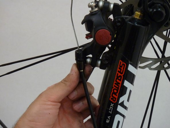 Unscrew the slotted brake cable cap on the rear tire and pull out the cable. Remove the cap from the cable.