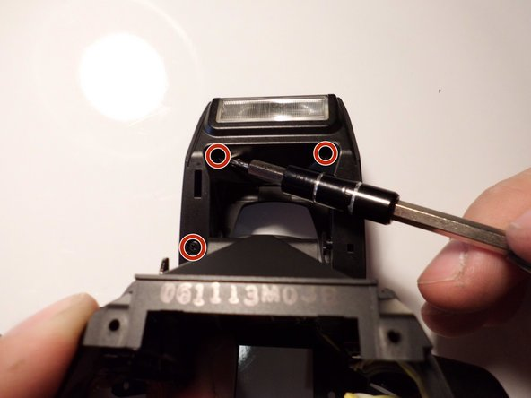Using the J00 bit, remove the three Phillips head 3 mm screws on the flash cap