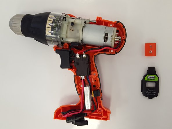 Gently remove the orange plastic speed switch from the drill.  It is located right above the motor.