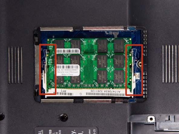 Locate the two metal levers on either side of the memory chip.