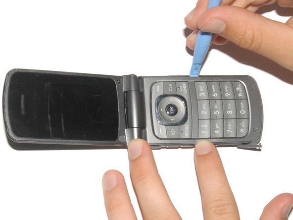 Soulevez prudemment le support du téléphone à l'aide d'un outil d'ouverture en plastique.