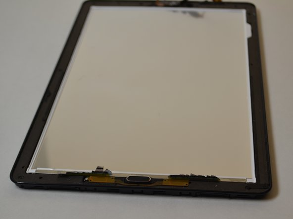 Slide the plastic opening tool around the perimeter while prying upwards until the screen separates from the bezel.